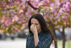 Woman having symptoms of spring pollen allergy. Young pretty woman having allergy symptoms in front o blooming tree in spring Stock Images