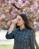 Woman having symptoms of spring pollen allergy. Young pretty woman having allergy symptoms in front o blooming tree in spring Royalty Free Stock Images