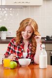 Young pretty woman having a bowl of cereal with Royalty Free Stock Photos