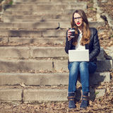 Young pretty woman having coffee break on stairs Royalty Free Stock Photography