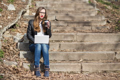 Young pretty woman having coffee break on stairs Royalty Free Stock Photo