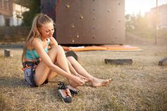 Young pretty woman having a trauma with foot after climbing practice on rock wall. Upset female climber rubbed her. Young pretty woman having a trauma with knee Royalty Free Stock Photography
