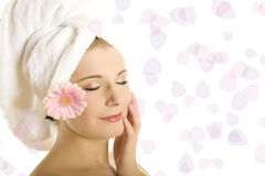 Young pretty woman with healthy pure skin. Close-up portrait of Young beautiful woman with healthy pure skin and wet hair in a towel holding pink gerber flower Royalty Free Stock Images