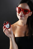 Young and pretty woman with heart shaped glasses and heart-shape alarm clocker on black background. Vertical Royalty Free Stock Photos