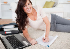 Young pretty woman with her laptop while writing Stock Photo