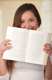 Young Pretty Woman Hiding Behind Open Book.  Stock Image