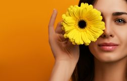 Young pretty woman hold yellow gerbera flower in green dress Royalty Free Stock Image