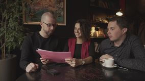 Young pretty woman holding a business plan to discuss it with two men. Business meetings in the cafe between three acquaintances. A young woman holding a stock footage