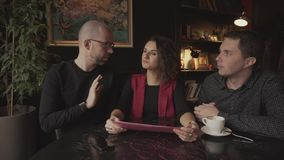 Young pretty woman holding a business plan to discuss it with two men. A young pretty woman holding a business plan to discuss with the two men sitting next to stock footage