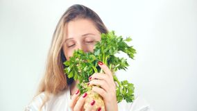 Young pretty woman holding fresh celery root. Young pretty blue-eyed woman holding in hands with red manicure fresh celery root and smiling at camera stock footage