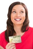 Young pretty woman holding golden plastic bank card. And planning her spending Royalty Free Stock Images