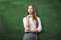Young pretty woman is holding her glasses and smiling on green chalkboard background stock images