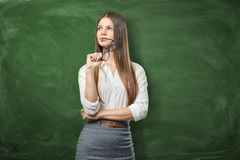 Young pretty woman is holding her glasses and thinking on green chalkboard background stock images