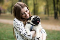 Young pretty woman holding her pet pug dog in the park stock photos