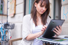 Young pretty woman holding Ipad looking away. Royalty Free Stock Photo