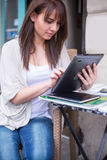 Young pretty woman holding Ipad looking away. Royalty Free Stock Photography
