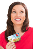Young pretty woman holding plastic bank card. And planning her spending Royalty Free Stock Photos
