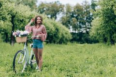 Young pretty woman holding retro bicycle with wicker basket full of flowers. In forest royalty free stock image