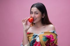 Young pretty woman holding a ripe tomato Royalty Free Stock Photography
