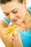Young pretty woman holding a slice of pizza. In her hands Royalty Free Stock Photography