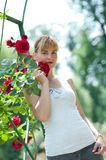 Young pretty woman holding and smelling red rose. Royalty Free Stock Photo