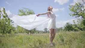 Young pretty woman holding white cloth on wind. Full length shot stock video footage