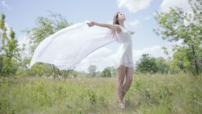Young pretty woman holding white cloth on wind. Full length shot stock video