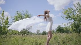 Young pretty woman holding white cloth on wind. Full length shot stock footage