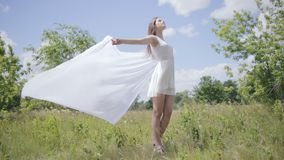 Young pretty woman holding white cloth on wind. Full length shot. Slow motion stock video