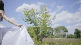 Young pretty woman holding white cloth on wind. Medium shot stock video footage