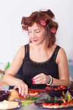 Young pretty woman housewife cooking with curler hair Stock Photos