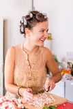 Young pretty woman housewife cooking with curlers on hair Royalty Free Stock Photography