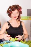 Young pretty woman housewife cooking with curlers Royalty Free Stock Photos