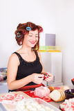 Young pretty woman housewife cooking with curlers Stock Image