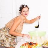 Young pretty woman housewife cooking with curlers hair Stock Images