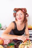 Young pretty woman housewife cooking with curlers hair Royalty Free Stock Image