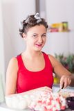 Young pretty woman housewife cooking with curlers hair Stock Photo