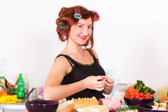 Young pretty woman housewife cooking with curlers hair Royalty Free Stock Photo
