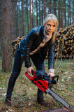 Young pretty woman with huge red chainsaw Stock Photos
