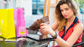 Young pretty woman with ipad holding wallet. She is siting in cafe. Royalty Free Stock Photos