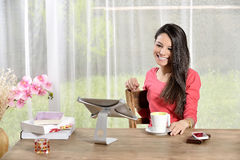 Young pretty woman Ipad looking away. Young pretty woman holding cup of coffee and Ipad looking away. mobile phone on the table Stock Image