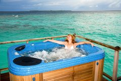 Young pretty woman in jacuzzi on background of oce Royalty Free Stock Photography