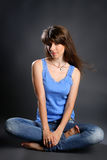 Woman in jeans  smiling and sitting on the floor Royalty Free Stock Photography