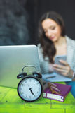 Young pretty woman with laptop and alarm clock on table Stock Photo