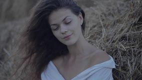 Young pretty woman leaning hay. Cinemagraph stock footage