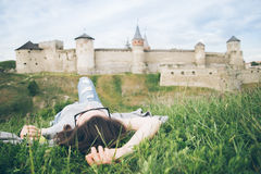 Young pretty woman lie in fron of old castle Royalty Free Stock Photography