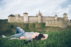 Young pretty woman lie in fron of old castle Stock Image
