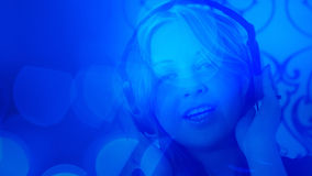 Young pretty woman listening music blue light background Royalty Free Stock Image