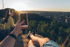 Young pretty woman listing music on the top of the hill with boyfriend. Young pretty women listing music on the top of the hill with boyfriend on sunset Stock Photos