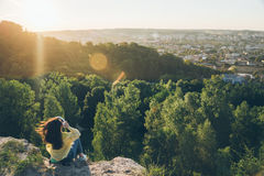 Young pretty woman listing music on the top of the hill. On sunset Stock Image